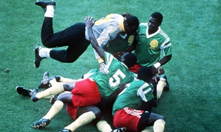 Cameroon players pile on top of each other as they celebrate the only goal